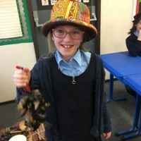 A student at  Keser Torah in Gateshead holding  goats' hooves, used as an instrument