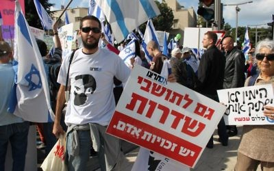 """Im Tirtzu activist holding a sign reading """"The residents of Sderot also have Human Rights"""""""