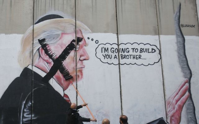 A Palestinian paints over a mural of the U.S. President Donald Trump during a protest in Bethlehem, West Bank,    (AP Photo/Nasser Shiyoukhi)