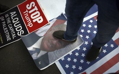A Palestinian steps on a poster of U.S. President Donald Trump and a representation of the American flag during a protest against the U.S. decision to recognise Jerusalem as Israel's capital, in Gaza City T  (AP Photo/ Khalil Hamra)