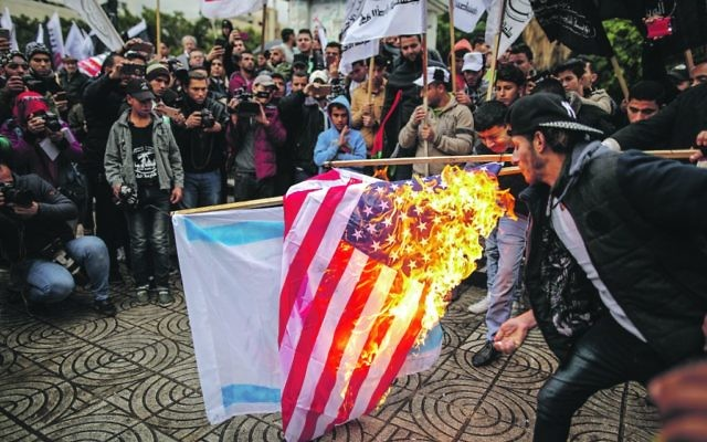 American and Israeli flags are burned by protesters