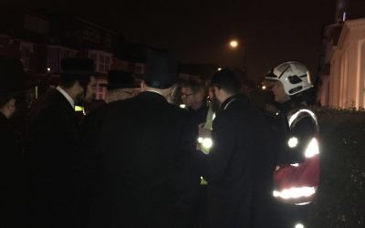 Members of the Charedi community speak with firefighters following the fire on the last night of Chanukah