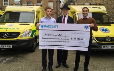 Yehudah Roitenbarg and Benjamin Cohen presenting their cheque to Hatzola