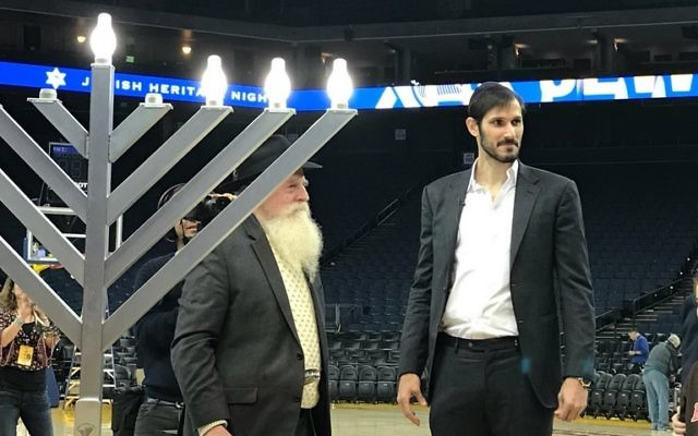Omir Casspi lit the menorah on court, having helped the Golden State Warriors to victory over the Dallas Mavericks