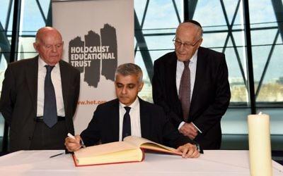 Holocaust survivors Ben Helfgott and Manfred Goldberg  besides Mayor of London Sadiq Khan, as he signs the Holocaust Educational Trust (UK) Book of Commitment at City Hall.