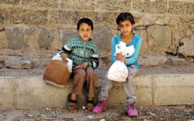 Children [not related to this article] affected by the ongoing crisis wait to receive food from a charity food distributing centre in Sana'a, Yemen