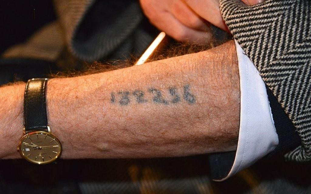 A Holocaust survivor displaying his arm tattoo