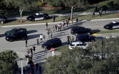 Students hold their hands in the air as they are evacuated by police from Marjory Stoneman Douglas High School in Parkland, Fla , after a shooter opened fire on the campus.   (Mike Stocker/South Florida Sun-Sentinel via AP)