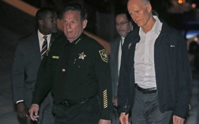 Florida Gov. Rick Scott, right, walks with Sheriff Scott Israel of Broward County to a news conference near Marjory Stoneman Douglas High School in Parkland, Fla., (AP Photo/Wilfredo Lee)