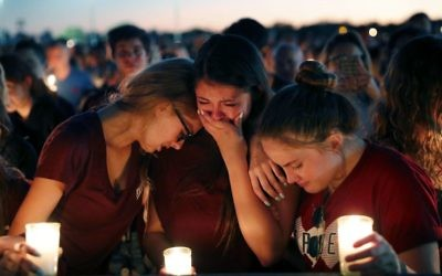 Students console each other as they weep during a candlelight vigil for the victims of the Wednesday shooting at Marjory Stoneman Douglas High School, in Parkland, Fla.,   (AP Photo/Gerald Herbert)