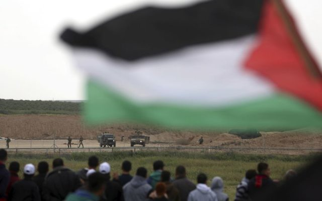 Protesters, one holding a Palestinian flag, stand in front of Israeli soldiers during a demonstration near the Gaza Strip border with Israel, in eastern Gaza City, Friday, March 30, 2018. (AP Photo/ Khalil Hamra)
