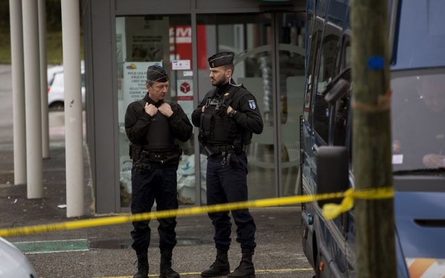 Police officers stand guard following an attack on a supermarket in Trebes, in southern France