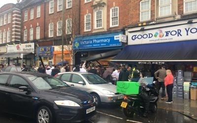 Pedestrians crowd around the pharmacy in Golders Green where the accident took place.   Image posted by David Collier on Twitter