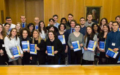 Graduates of the programme holding their certificates at ceremony in parliament