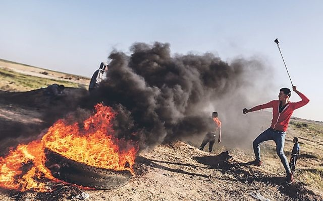 Protesters run during clashes with Israeli security forces following a demonstration near the border with Israel in the southern Gaza Strip   (Photo by Momen Faiz/NurPhoto/Sipa USA)