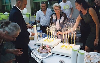 Members of the JCC celebrate its 10th anniversary with a cake and sparklers