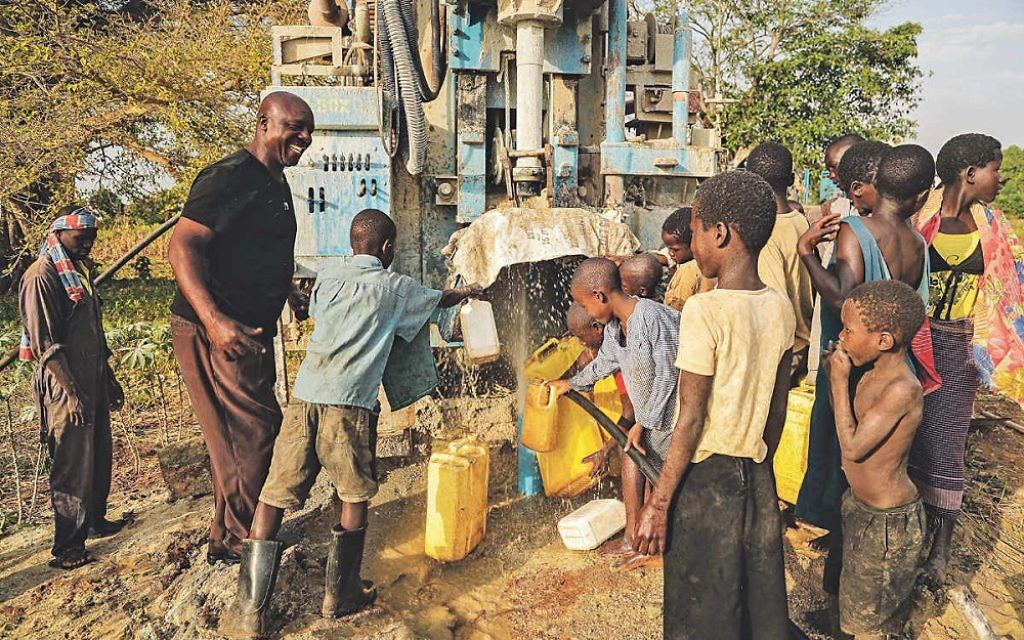 Villagers gather round their new water pumping system