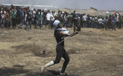 A Palestinian protester slings a stone towards Israeli troops during a protest at the Gaza Strip's border with Israel, Monday, May 14, 2018 . (AP Photo/Khalil Hamra)