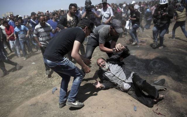 An elderly Palestinian man falls on the ground after being shot by Israeli troops during a deadly protest at the Gaza Strip's border with Israel, east of Khan Younis, Gaza Strip,  (AP Photo/Adel Hana)