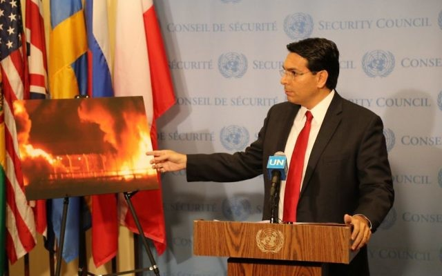 Danny Danon at the United Nations displaying a picture of the Gaza crossing used to bring in humanitarian aid, lit up in flames.