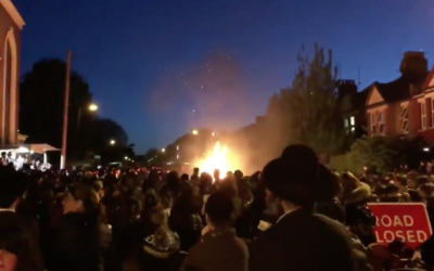 Orthodox community members watch on shortly after the explosion of the Lag Baomer fire  Screenshot from Youtube