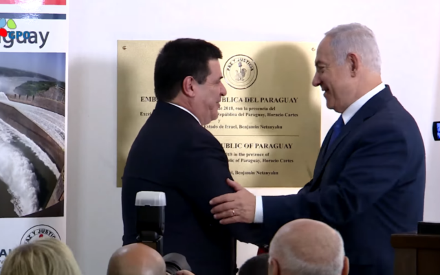 PM Benjamin Netanyahu embraces President Horacio Cartes after unveiling a plaque at the Embassy dedication