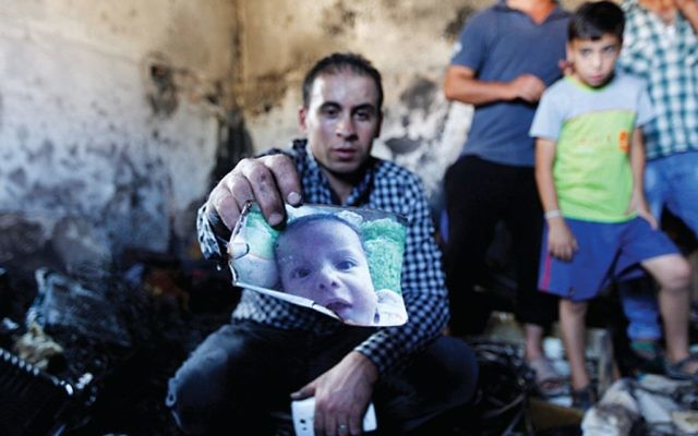 A relative holds up a photo of a one-and-a-half year old boy, Ali Dawabsheh, in a house that had been torched in a suspected attack by Jewish settlers in Duma village near the West Bank city of Nablus, Friday, July 31, 2015. T (AP Photo/Majdi Mohammed)