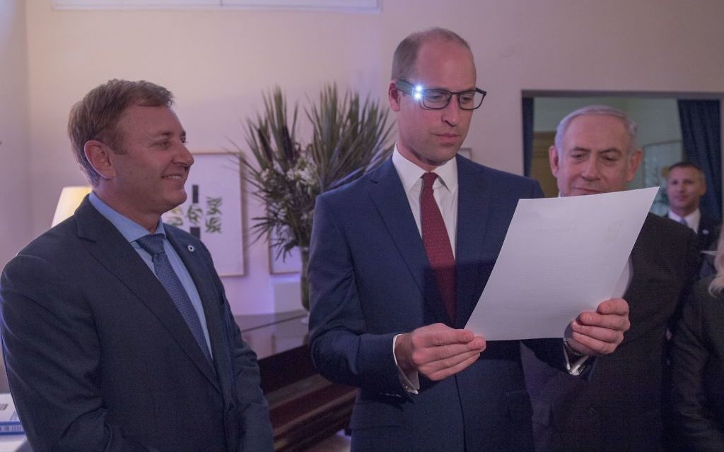 The Duke of Cambridge (centre), with Israeli Prime Minister Benjamin Netanyahu (right) and inventor Ziv Aviram (left) as he tries on glasses linked to a computer to help partially sighted people to see more clearly, during a Garden reception at the UK Ambassador to Israel in Tel Aviv, Israel   Photo credit : Arthur Edwards/The Sun/PA Wire