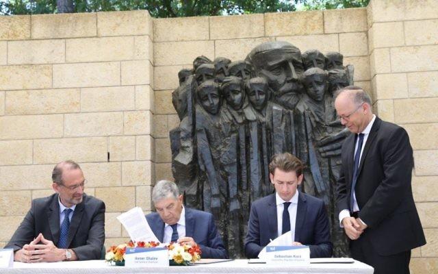 Sebastian Kurz and Yad Vashem's chair Avner Shalev signing the historic agreement.   Credit: @yadvashem on Twittr