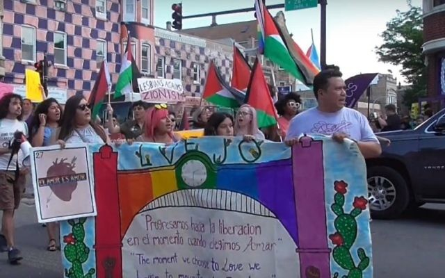 Participants in the 2018 Chicago Dyke March waving Palestinian flags. (Screenshot of Windy City Times video)