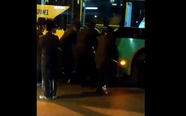 Screenshot from video of the incident, shows Charedi men ripping off a poster from a bus, showing their opposition to  Rachel Azaria's candidacy