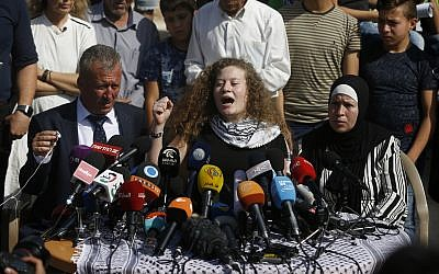Ahed Tamimi speaks sitting between her father Bassam and mother Nariman during a press conference on the outskirts of the West Bank village of Nabi Saleh near the West Bank city of Ramallah,  (AP Photo/Majdi Mohammed)