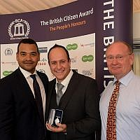 Dr Asher Lewinsohn (centre) collects his award, flanked by TV presenter and awards host Michael Underwood (left) and BCA Ambassador Des Benjamin (right)