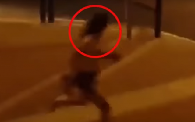 """A screen capture from a video of a young woman being chased in Beit Shemesh by a group of ultra-Orthodox men over her """"immodest"""" clothes. (Screen capture: YouTube)"""