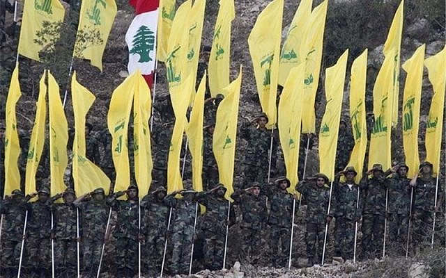 Hezbollah flags paraded at a rally, with one Lebanese flag