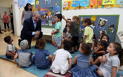 Israeli prime minister Bibi Netanyahu speaks with small children in a southern Israeli community