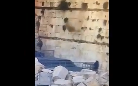 Screenshot shows video footage of the boulder dropping from the Kotel