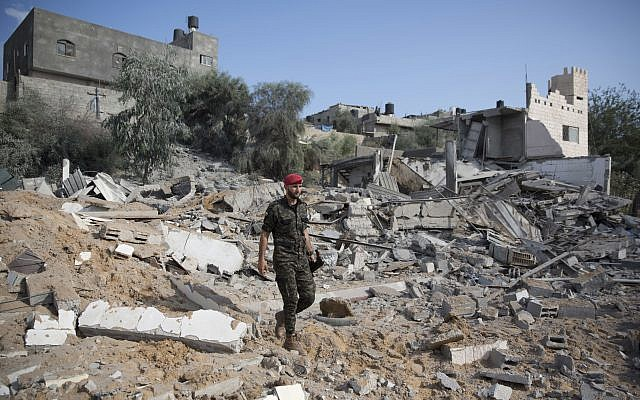 A Palestinian Hamas military policeman walks over the rubble of a site hit by Israeli airstrikes in Gaza City,  (AP Photo/Khalil Hamra)