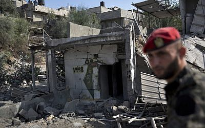 A Palestinian Hamas military policeman inspects the damage caused by Israeli airstrikes in Gaza City, Thursday, Aug. 9, 2018. Israel struck targets in the Gaza Strip after dozens of rockets were launched Wednesday from the coastal territory ruled by the Islamic militant Hamas group, the Israeli military said. (AP Photo/Khalil Hamra)