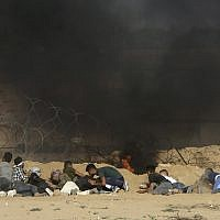 Protesters take cover from shooting and teargas fired by Israeli troops near the fence of the Gaza Strip border with Israel, during a protest east of Khan Younis, southern Gaza Strip, Friday, Aug. 17, 2018.    (AP Photo/Adel Hana)