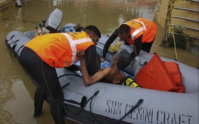 Indian military personnel rescue a flood affected man in the southern state of Kerala, (Indian Navy, via AP)