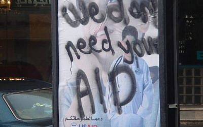 "A poster in the West Bank from 2007 for USAID, daubed with graffiti on it saying ""We don't need your AID"""