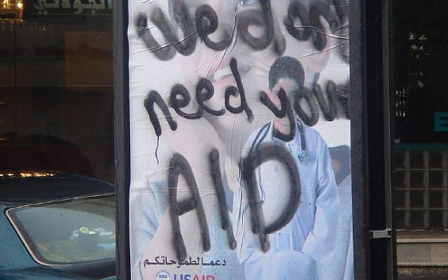 """A poster in the West Bank from 2007 for USAID, daubed with graffiti on it saying """"We don't need your AID"""""""