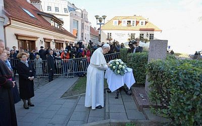 Pope laying a wreath before praying at the site