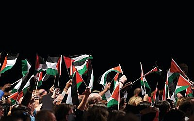Delegates hold up Palestinian flags during a debate on the third day of the Labour party conference in Liverpool  (Photo creditOLI SCARFF/AFP/Getty Images)