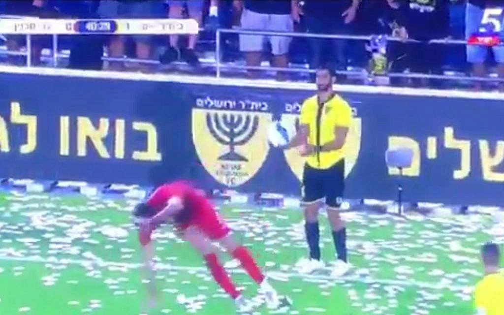 The Bnei Sakhnin player goes to ground, while Ofir Kriaf waits to take a throw in