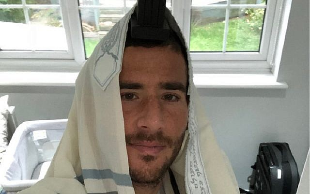 Tomer Hemed donning his tefillin prior to the start of Yom Kippur