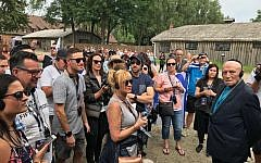 Group listens to a tour guide at Auschwitz