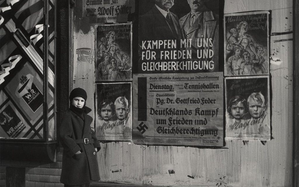 "Vishniac's daughter, Mara, posing in front of an election poster for Hindenburg and Hitler that reads ""The Marshal and the Corporal: Fight with Us for Peace and Equal Rights"", Berlin, 1933. Credit: Mara Vishniac Kohn"