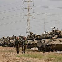 Israeli soldiers seen walking next to Merkava tanks t stationed in an open area near Israel's border with the Gaza Strip in October  2018. Photo by: JINIPIX